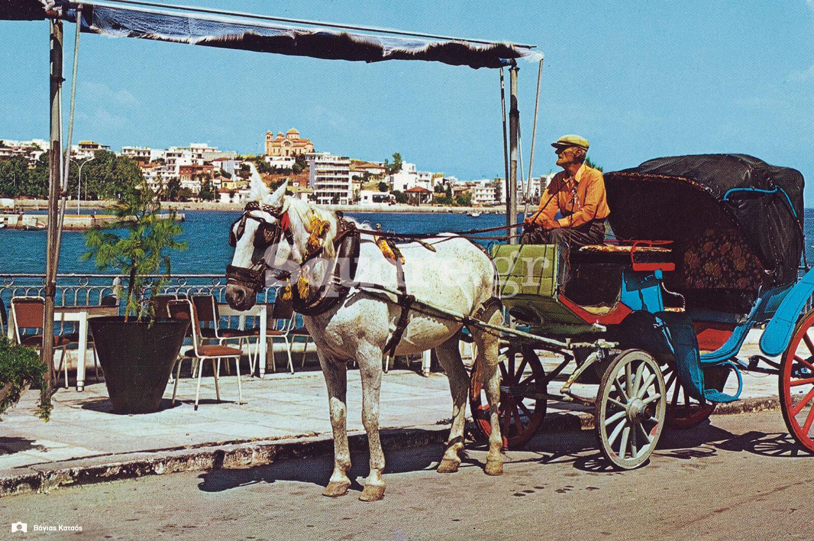 5-Ένας-αμαξάς,-σταματημένος-μπροστά-από-του-Μανώλη-του-«τρελού»,-με-φόντο-τα-τραπεζοκαθίσματα-του-καφενείου